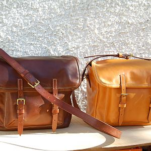 A pair of Sedgwicks bridle panel hide satchels, with bridle butt strapping and shoulder straps, machine stitched. London colour and conker