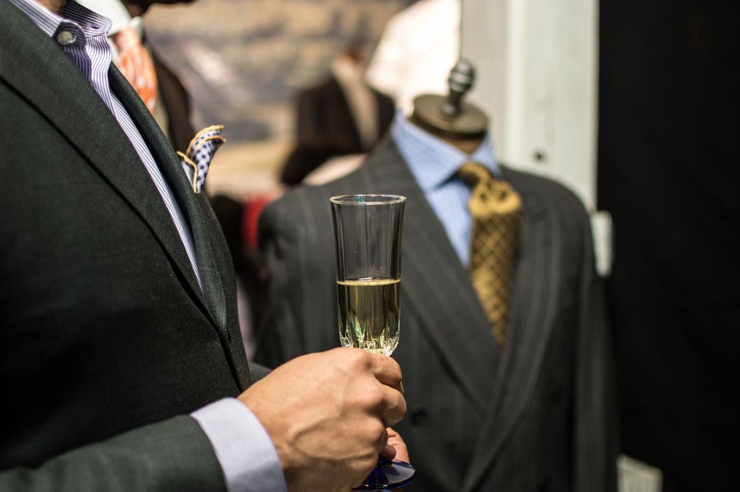 Client purchased bespoke suit enjoying a glass of wine while getting advice from one of the fitters.